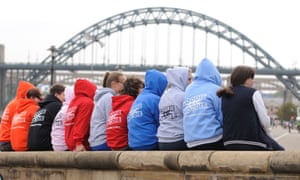 A group of young people wearing coloured hooded tops in front of a bridge
