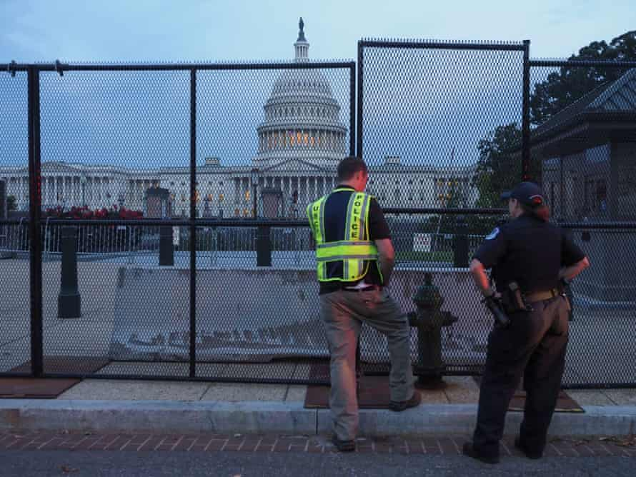 Capitol police officers look over the integrity of the fence put up to secure the US Capitol and its grounds before Saturday's rally.