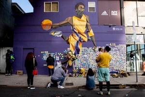Fans pay their respect with notes and a makeshift memorial next to a mural in Los Angeles.