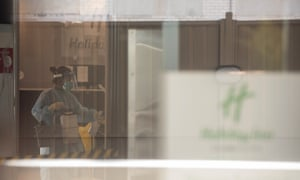 Cleaners wearing full PPE disinfect the Holiday Inn hotel near Melbourne airport.