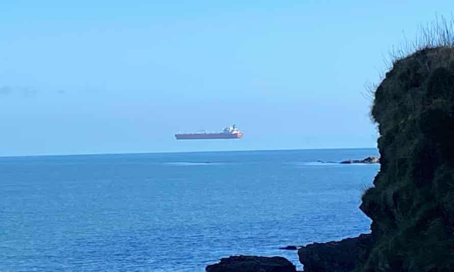 A tanker appears to hover high above the surface of the sea off the Cornish coast.