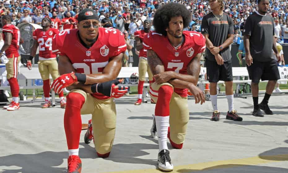 Colin Kaepernick, right, and Eric Reidkneel during the national anthem before an NFL football game in protest against police brutality.