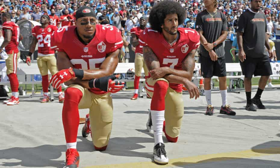 Colin Kaepernick (right) and Eric Reid kneel during the national anthem before the 49ers' game against the Panthers