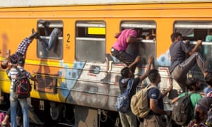 Migrants try to board a train