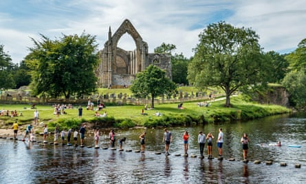 People enjoy the weather and moderate social distancing on the stepping stones across the River Wharfe in Bolton Abbey, North Yorkshire. High temperatures are expected to continue on Sunday.