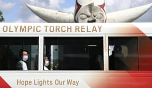 Tokyo 2020 Olympic torch relay runners wearing protective masks wait in a bus in Osaka