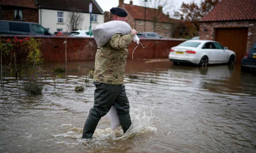 Soldiers help with sandbagging homes in the village of Fishlake last week.