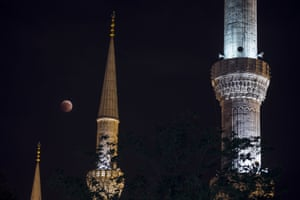 The blood moon appears to dangle between minarets in Istanbul, Turkey.
