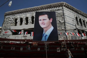 A man walks past a large banner of the Syrian president, Bashar al-Assad, in Douma.