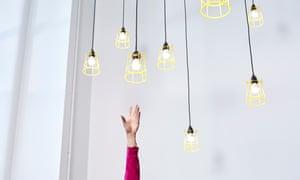 A hand reaching for lightbulbs