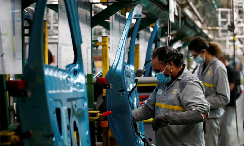 Employees wearing protective face masks work on a Renault assembly line in France.