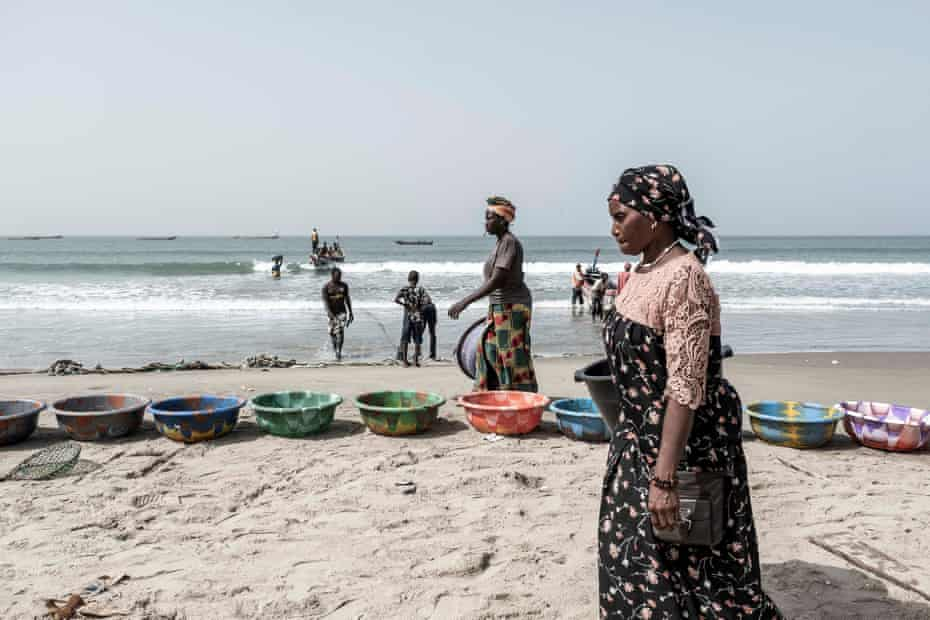 Women get ready to buy fish as the canoes come back to the shore at Gunjur village