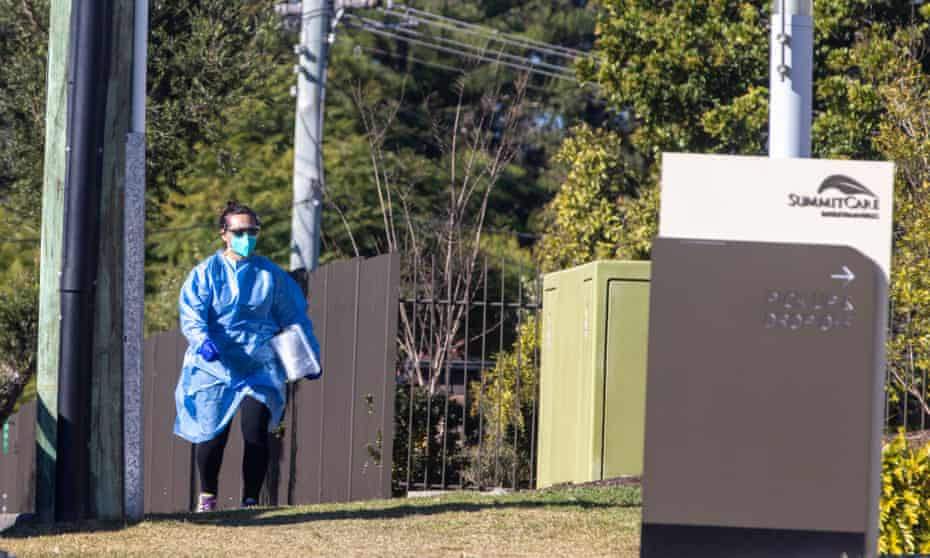 A person in PPE arrives at SummitCare aged care facility in Sydney's Baulkham Hills on Sunday after it was revealed three residents had tested positive to Covid-19. Two staff members were infected last week.