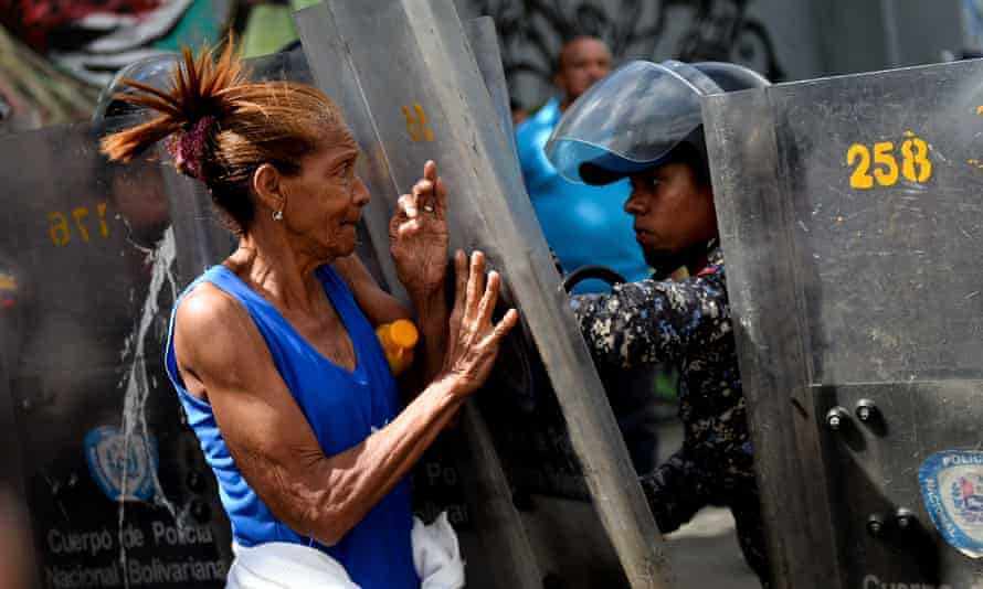 A protestor is confronted by Venezuelan security forces