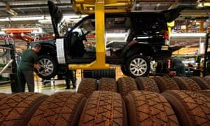 A worker puts the wheels on a Land Rover Discovery at its factory in Solihull