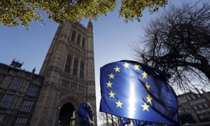 The sun shines through European Union flags tied to railings outside parliament in London