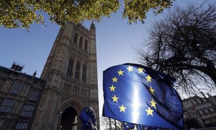 The sun shines through an EU flag outside the Houses of Parliament.