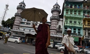 A Buddhist monk and a Muslim walk past the Bengali Sunni Jameh mosque in Yangon