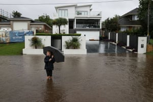 A child wades through floodwaters on a street near the Nepean River