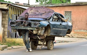 A man transports the body of a car on a two-wheeled carriage in Abidjan, Ivory Coast