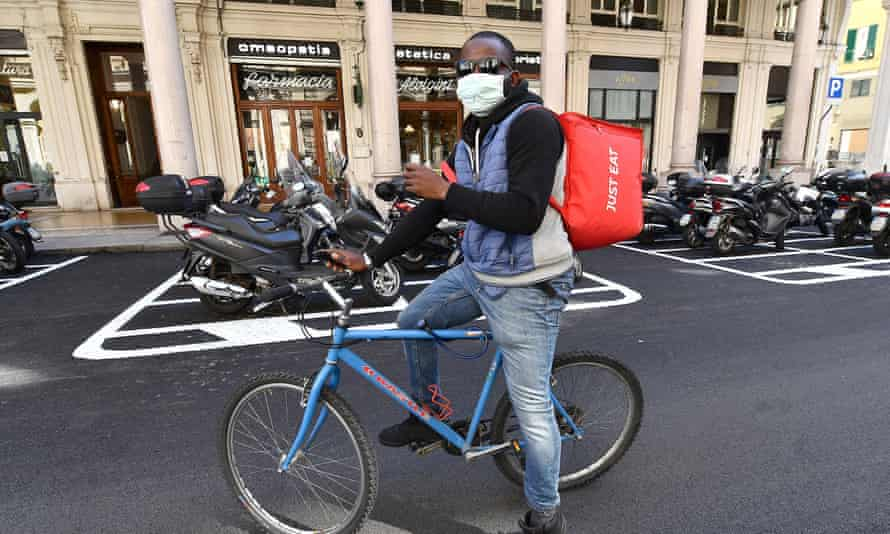 A delivery rider in Genoa, Italy, 19 March 2020: 'Uniting against the pandemic in a show of spontaneous patriotism ultimately makes the nation more cohesive.'