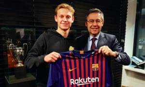 Frenkie de Jongposes with a Barcelona shirt and his new club's president, Josep Maria Bartomeu, after ending months of transfer speculation by agreeing to join Barcelona in July.