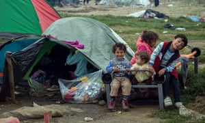 Syrian children play outside a tent at a camp in northern Greece