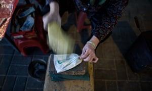 A villain hitter beats a paper effigy with her shoe