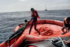 A man helps another into one of the Proactiva Open Arms rescue inflatables