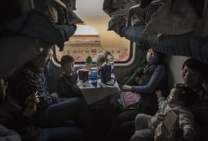 A family rides on a crowded train. Road and rail are the most popular ways to travel for the holiday leading to packed trains