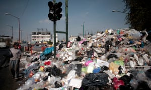 A man walks past piled rubbish in Mexico City.