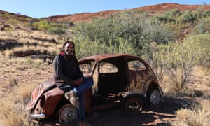 Robert Fielding with a rusted abandoned car at Mimili, SA