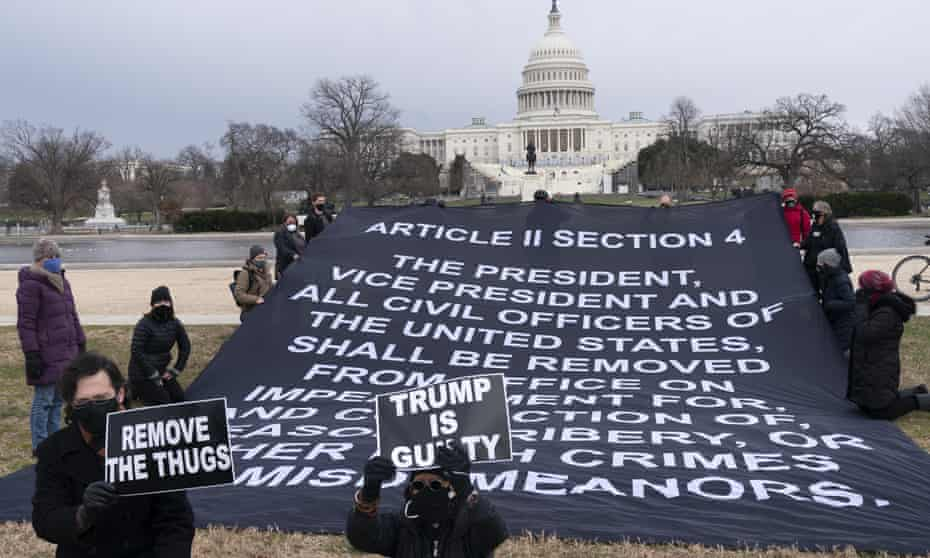 In response to riots at the Capitol on Wednesday, a group holds a large banner urging President Donald Trump to be removed from office