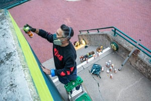 Remi Rough working on a mural in Halifax