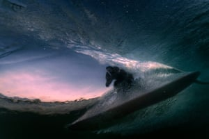 A surfer seen through a wave at night