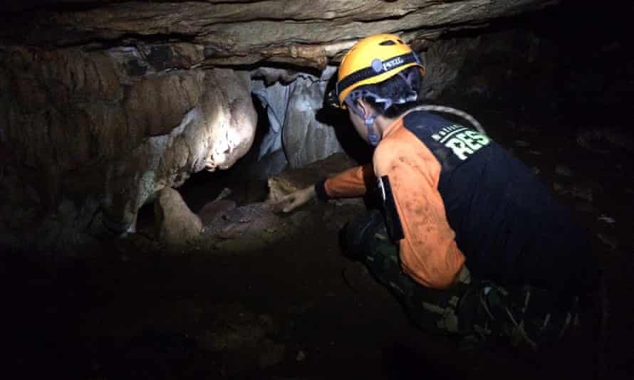 Thai rescue officers search for alternative entrances during the rescue operation for missing football players in Tham Luang cave.