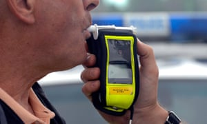 Close up of a police breathalyser being used on a man (posed by a model).