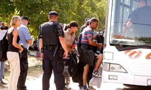 Refugees board buses transferring them to Hungary and Austria at the Croatian-Serbian border near Tovarnik, Croatia.