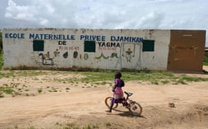 A girl rides her bicycle in the front of a school in the village of Yagma, north of Ouagadougou, on 17 September 2019.