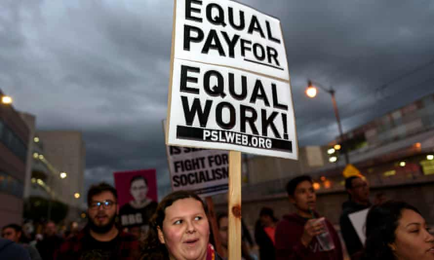 An activist seen holding a placard that says equal pay for equal work during the International Women's Strike in Los Angeles.