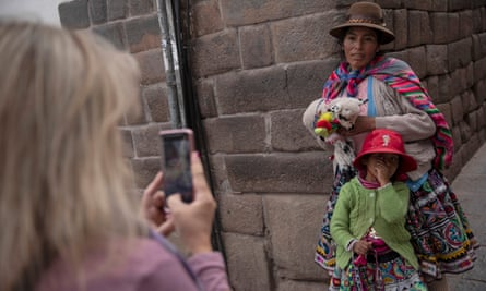 A Quechua woman and child have their photographs taken by a tourist for money in Cusco, Peru.