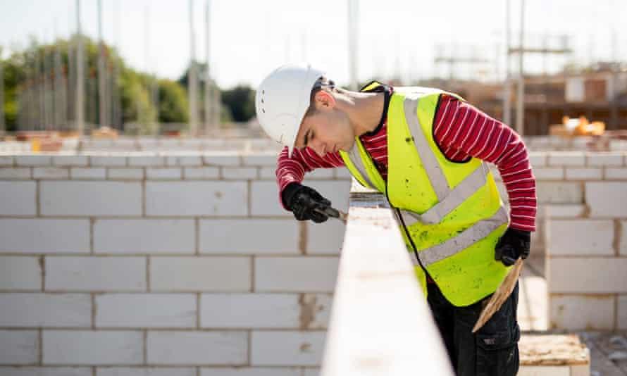 A workman lays concrete bricks