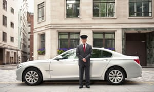 A chauffeur standing by a BMW