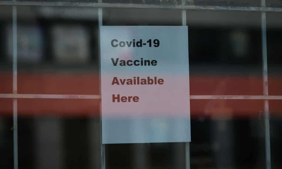A sign advertising the availability of the Covid-19 is displayed on the front door of a pharmacy in Edmonton, Canada.