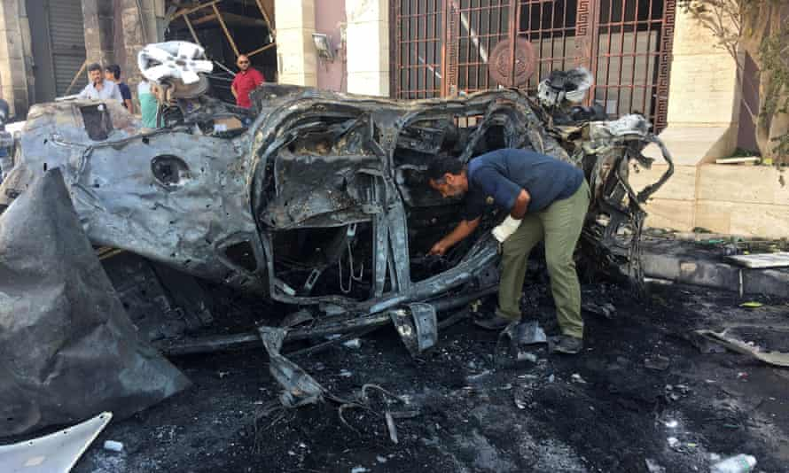 Security officials inspect the site where a car bomb exploded in Benghazi.