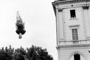A young man trampolines in front of the Town Hall building in Lugano
