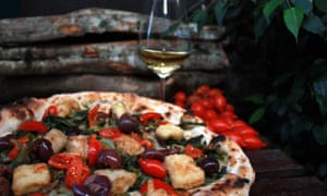 Olive pizza and a glass of wine on a table at Pizza Da Attilio, Napes, Italy.