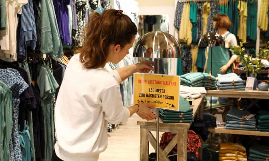 A shop in Prenzlauer Berg, Berlin, is prepared for its reopening with a warning to customers to maintain their distance between each other.