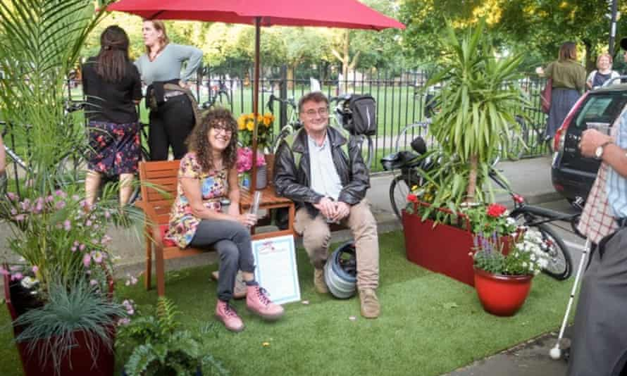 Parklet. Man and woman on bench in 'reclaimed' parking space