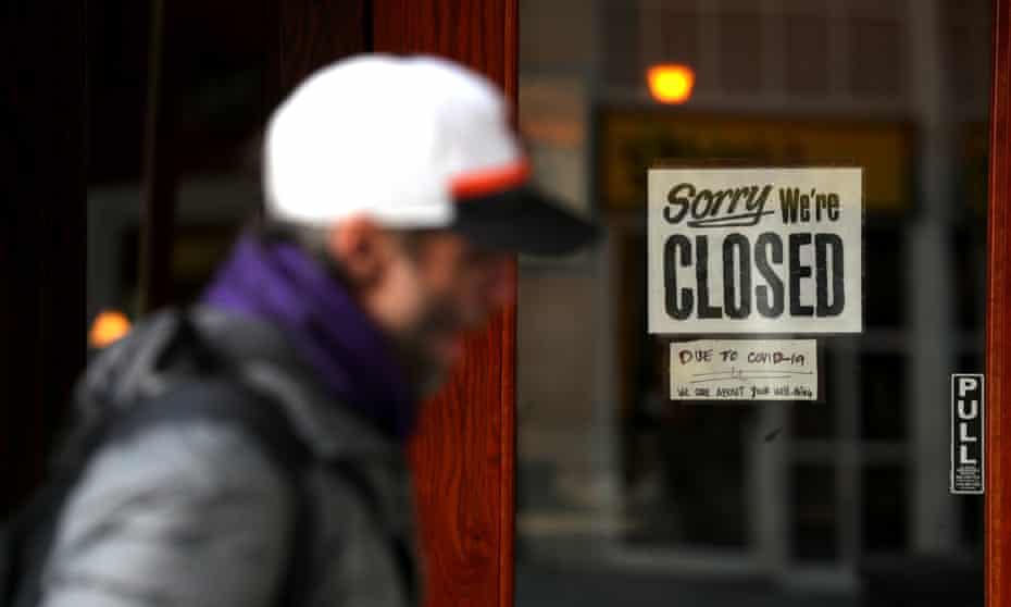 A pedestrian walks by a closed sign on the door of a restaurant in San Francisco.